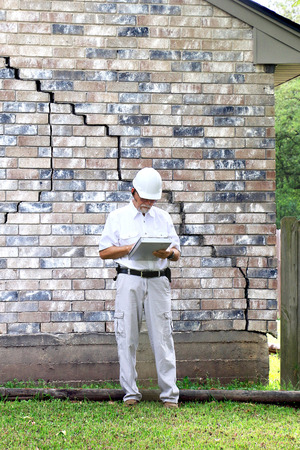 foundation cracks: Inspector inspecting home?s foundation is experiencing settlement (collapse). Eventually the brick veneer begins to separate from door and window frames. Finally framing and roof problems occur, as well as plumbing problems. Foundation problems don?t get  Stock Photo