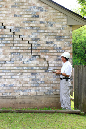 Inspector inspecting home?s foundation is experiencing settlement (collapse). Eventually the brick veneer begins to separate from door and window frames. Finally framing and roof problems occur, as well as plumbing problems. Foundation problems don?t get  Stock Photo