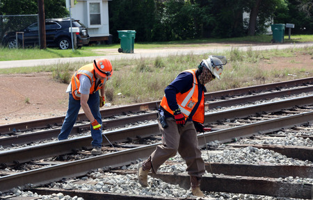 Men are marking railroad ties for workers to remove & install new ones