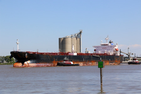 gallons: Super Tanker ship coming into port to deliver thousands of gallons of crude oil two tug boats are giding the ship.