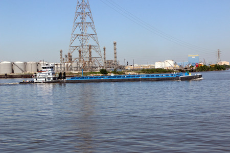 tug boat: Tug boat pushing large barge through the ship channel Stock Photo