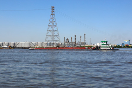 Tug boat pushing large barge through the ship channel Stock Photo