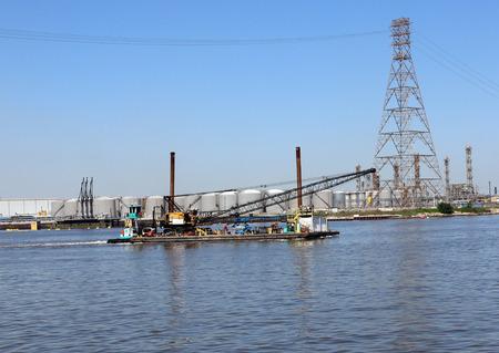 tug boat: Tug boat pushing large barge wirh crane through the ship channel Stock Photo