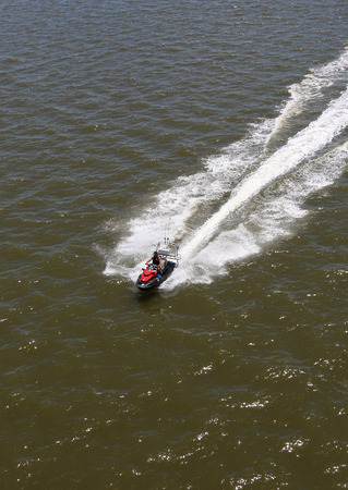 Aerial picture of Fisherman riding on personal watercraft looking for place to go fishing on the ocean photo