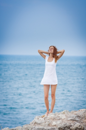 pretty girl in dress standing and looking to a sea