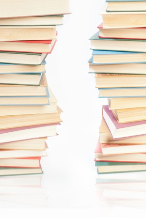 Two towers of books on white background photo