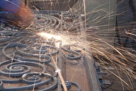 prefabricate: Worker welding metallic object . Production and construction