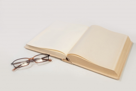 blank book with glasses isolated on white photo