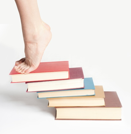 Person standing on a stack of books