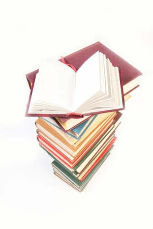 pile of books with one book open on white background photo