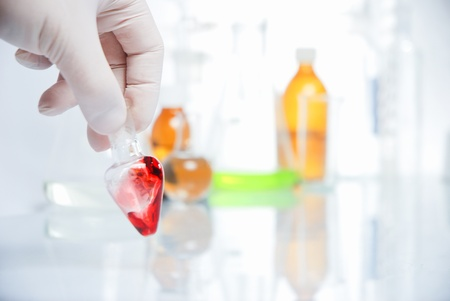 Doctors hand in glove with blood in laboratory Stock Photo