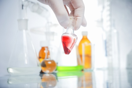 Doctor's hand in glove with blood in laboratory