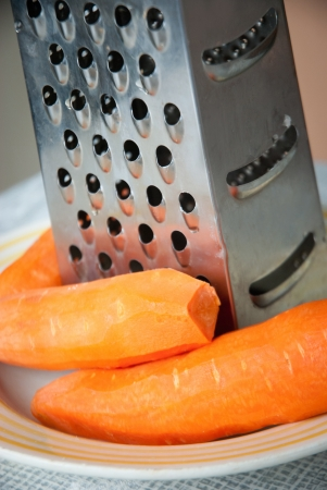 Carrot and grater for vegetables closeup photo