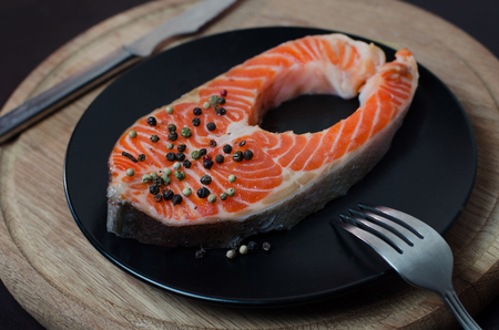 Fresh salmon steak on the black plate