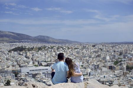Romantic couple sightseeing above Athens from Philosophical mountain