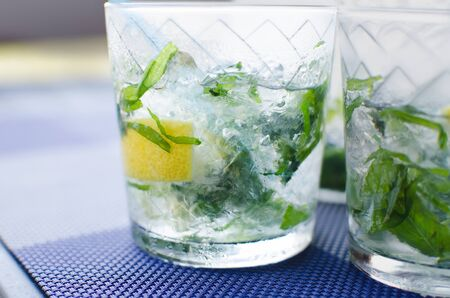 full glass of fresh cool transparent water with ice, lemon and , basil leaves on blue table