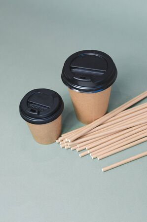 Craft coffee cups with paper straw on gray background. Eco friendly design. Zero waste, plastic free items