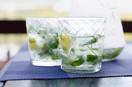 Two full glasses of fresh cool transparent water with ice, lemon and , basil leaves on blue table