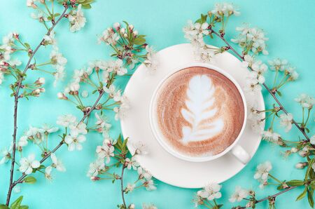 coffee cup with latte art and spring cherry blossom