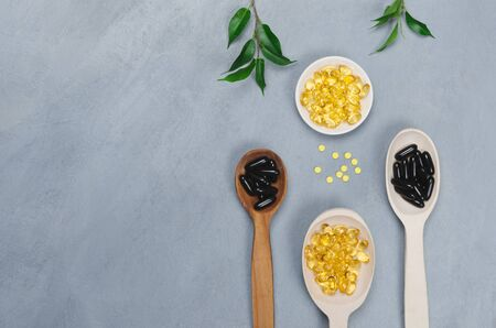 Black and yellow pills on wooden spoons on gray background Zdjęcie Seryjne