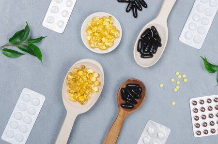 Black and yellow pills on wooden spoons or packed on gray background
