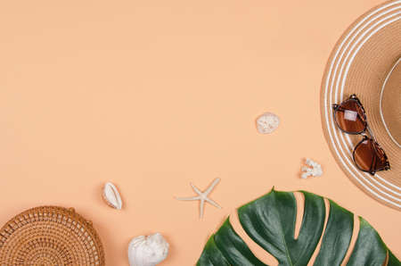 Summer straw hat, tropical monstera leaf, sunglasses, shells, starfish on yellow background. top view, copy space. Reklamní fotografie
