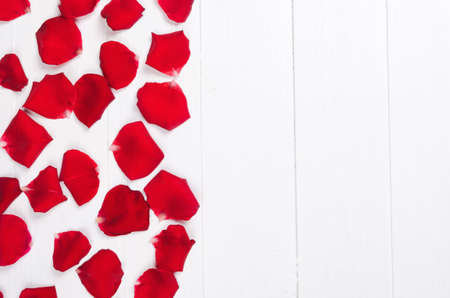 Red rose petals on white wooden background