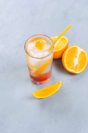 Orange alcohol cocktail with orange fruit slice on pink and gray background