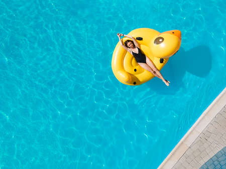 Top view aerial photo of a pretty model in black swimwear is enjoying pool in inflatable duck Standard-Bild