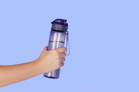 Reusable water bottle in a mans hand on blue background. Copyspace