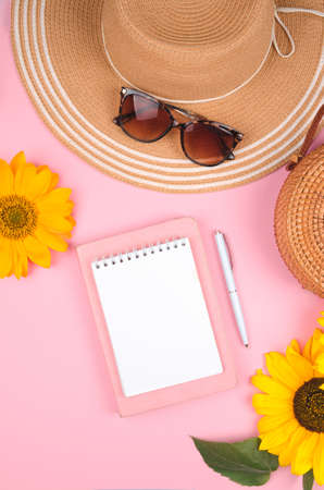 Creative flat lay of workspace desk, notepad and sunflower on pink background Standard-Bild