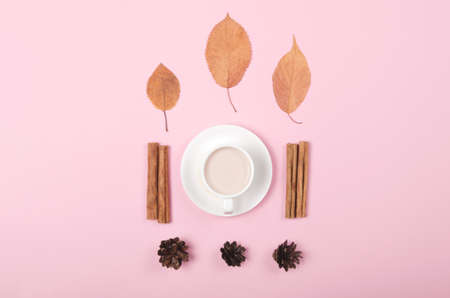 Autumn background with coffee, cinnamon and leaves on pink background