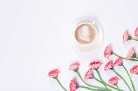 Coffee cup with latte art with pink flowers on white background