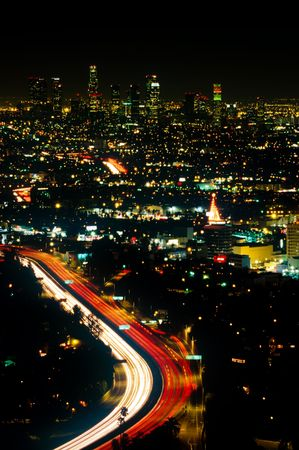 Red and white lights of traffic flowing through the bright lights of Los Angeles at night, seen form above. Stock Photo