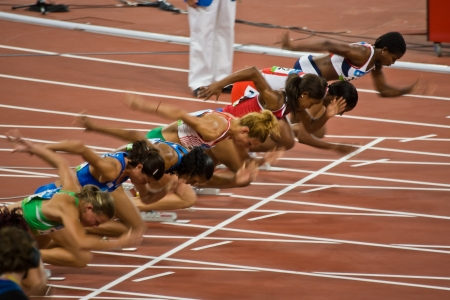 Beijing, China - 18 augustus 2008 OLYMPICS: Vrouwelijke atleten stijgen op bij het begin van de 100 meter race Stockfoto - 9891447