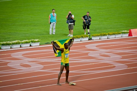 Beijing - Aug 16: Usain Bolt celebrates holding the Jamaican flag after setting new world 100 meter record  for men