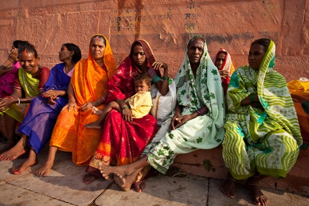 VARANASI, INDIA - JULY 22, 2009: Group of Indian women in colorful saris sit and watch the solar eclipse from the banks of the Ganges River July 22, 2009 in Varanasi, India.