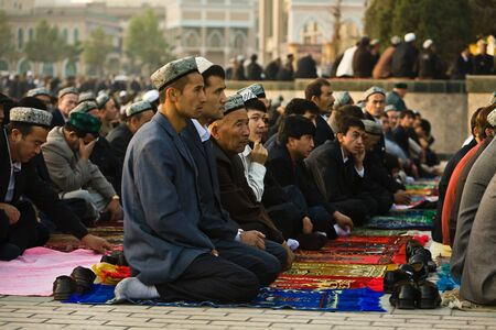 Kashgar, China - Oct 2: Uyghur men  kneeling outside Id Kah Mosque during service at the end of Ramadan. Kashgar, Xinjiang province, western China October 2, 2008