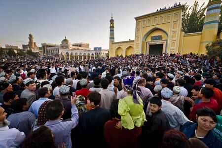 Kashgar, China - Oct 2: Crowd watches Uyghur men dance outside Id Kah Mosque after service at the end of Ramadan. Kashgar, Xinjiang province, western China October 2, 2008 Editorial