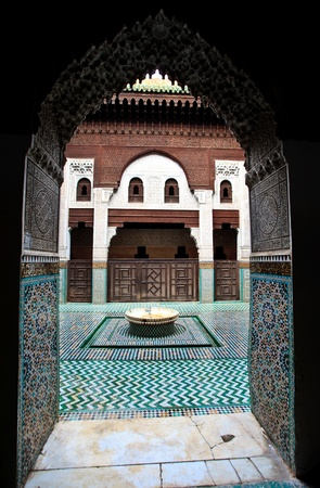 Meknes, Morocco: Intricate and symetrical interior of Muslim madrasah school framed by arched entrance in Meknes, Morocco.