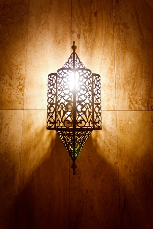 lit lamp: Morocco:  Ornate metal lamp in the wall of a mosque, Morocco. Stock Photo