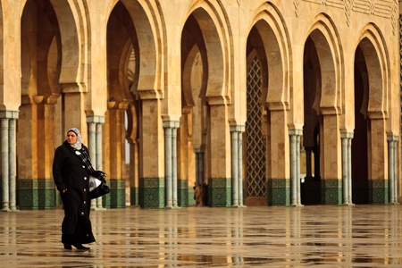 Casablanca, Morocco - Dec 19: Woman in long black coat walking in front of ornate arches of Hassan II Mosque,  December 19, 2009 Casablanca, Morocco.