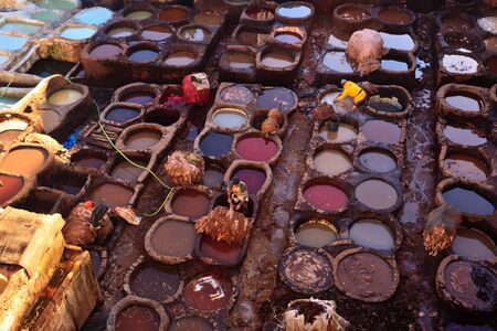 fez: Fez, Morocco - Dec 22: Colorful tanning pools and workers at a traditional leather tannery,  December 22, 2009 Fez, Morocco.