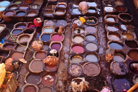 vats: Fez, Morocco - Dec 22: Colorful tanning pools and workers at a traditional leather tannery,  December 22, 2009 Fez, Morocco.