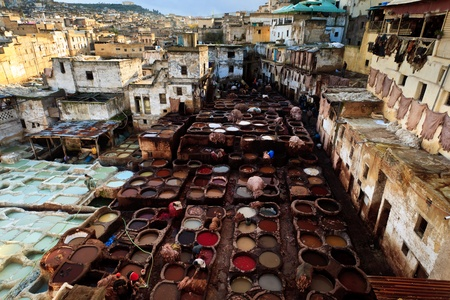 fez: Fez, Morocco - Dec 22: Colorful tanning pools of a traditional leather tannery amid residential houses in the old quarter medina,  December 22, 2009 Fez, Morocco.