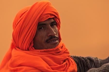 garb: Merzouga, Morocco - Dec 24: Portrait of Berber man in the Sahara with turban head garb blowing in the wind  December 24, 2009 Merzouga, Morocco. Editorial
