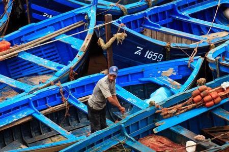 moorings: Essaouira, Morocco - Jan 13: Fisherman works among group of blue fishing boats January 13, 2010 Essaouira, Morocco.