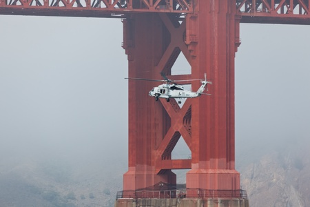 SAN FRANCISCO - OCTOBER 8: Helicopter from Aircraft carrier USS Carl Vinson passes under the Golden Gate Bridge during Fleet Week on October 8, 2011 in San Francisco, USA