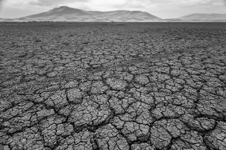 Cracked pattern of dry lake bed in Sahara Desert Morocco in black and white photo