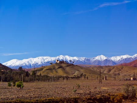 Mosque on hilltop with snow capped Altas Mountains in the background photo